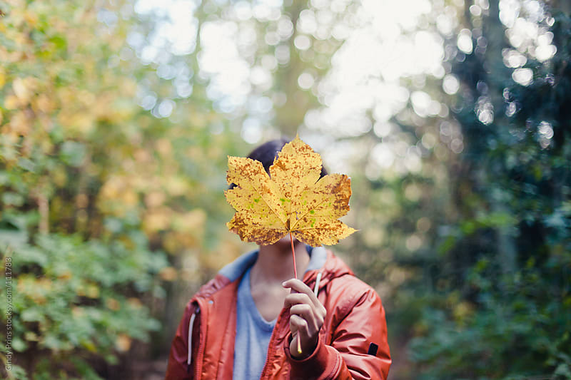 Teenage boy in an orange jacket holding a big autumn leaf in front of his head by Cindy Prins for Stocksy United