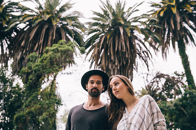 Young Couple Standing in Front of Many Palm Trees by Jayme Burrows for Stocksy United