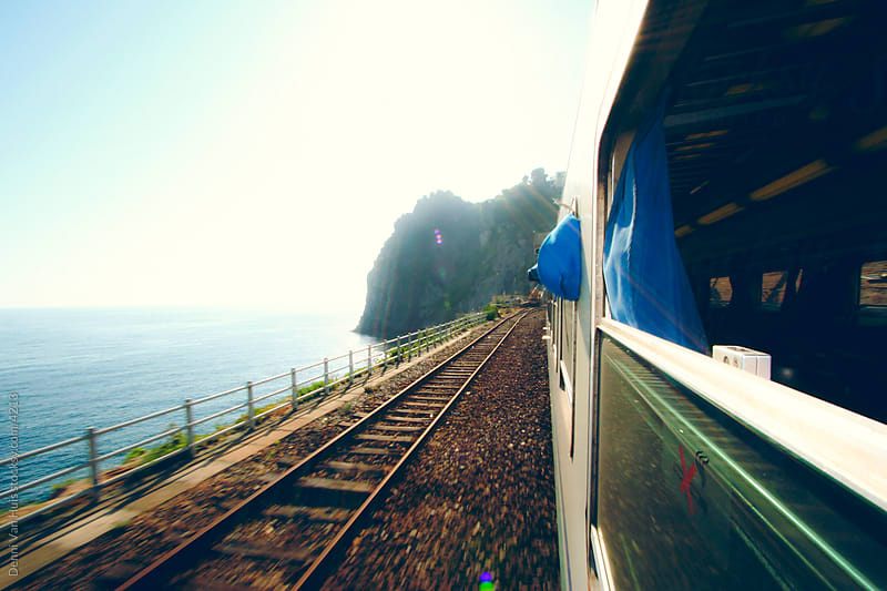 A moving train traveling along the coast of Italy with a view of the ocean. by Denni Van Huis for Stocksy United