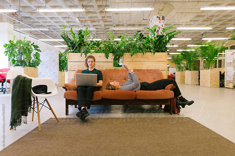 Two young women working, sketching and designing. Using a laptop, sitting on a couch. by Ivo de Bruijn for Stocksy United