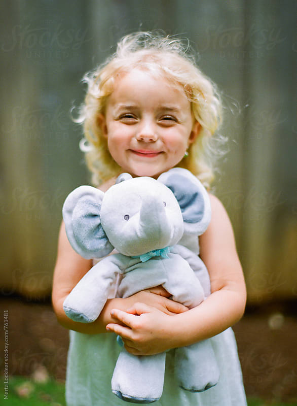 Little girl hugging a toy elephant by Marta Locklear for Stocksy United