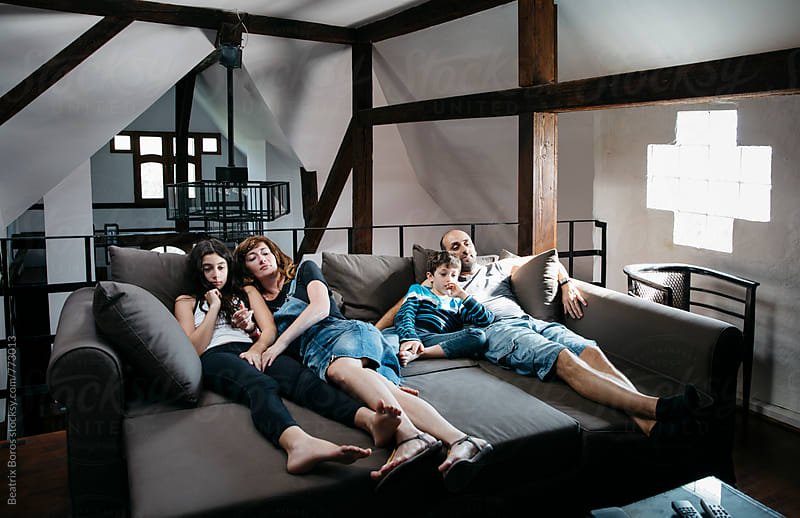 Mother with daughter and father with son watching a movie at home laying on the sofa by Beatrix Boros for Stocksy United