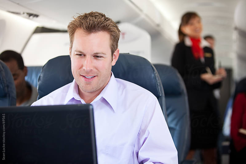 Airplane: Cheerful Businessman Getting Work Done on Plane by Sean Locke for Stocksy United
