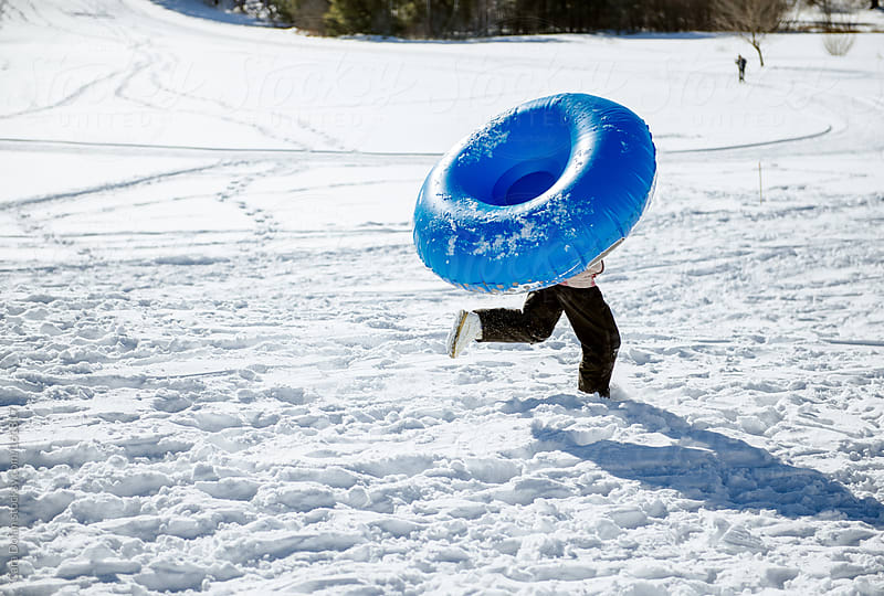 Child runs across snowy field with an inflatable sled over her head by Cara Dolan for Stocksy United