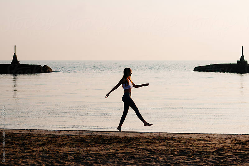 Woman walking on the beach at sunset by Susana Ramírez for Stocksy United