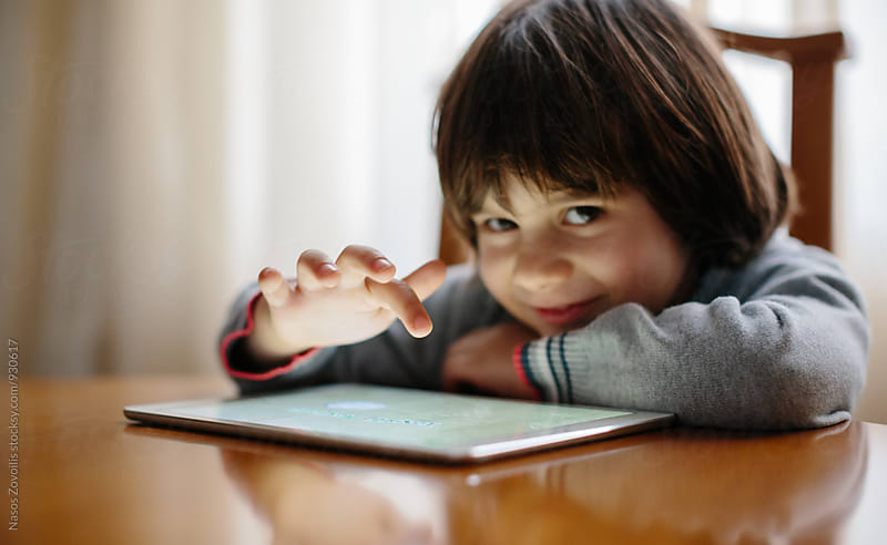Small boy smiling at camera while using a digital tablet by Nasos Zovoilis for Stocksy United