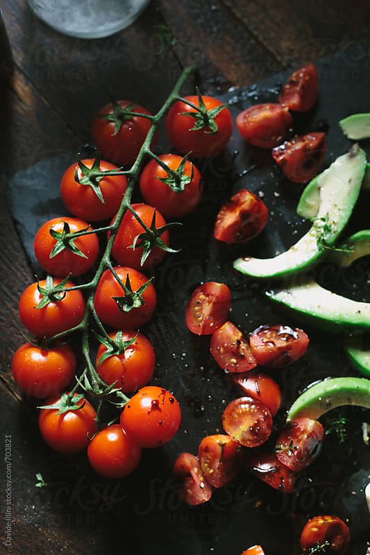 Cherry tomatoes and avocado by Davide Illini for Stocksy United