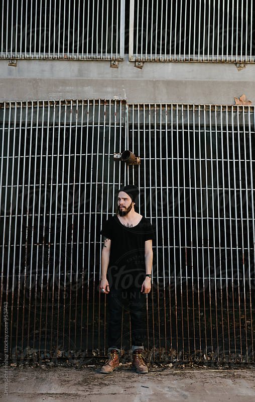 Young man in front of metal grate  by Drew Schrimsher for Stocksy United