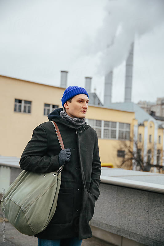 Man standing in front of chimneys of a factory in the city by Andrey Pavlov for Stocksy United