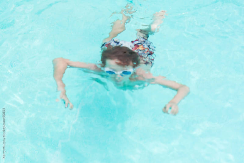 Young boy swimming underwater in pool by Kerry Murphy for Stocksy United