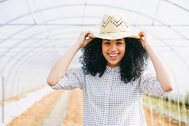 Portrait of a young woman smiling in a greenhouse. by BONNINSTUDIO for Stocksy United