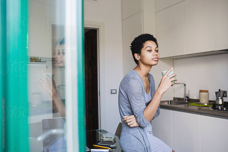 Young attractive African woman relaxing at home with a cup of coffee by michela ravasio for Stocksy United