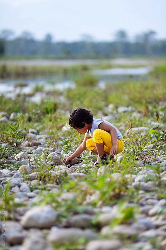 Little girl collecting stones on the riverbed by Saptak Ganguly for Stocksy United