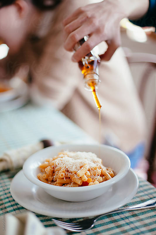 Woman hand pouring red pepper flavored olive oil on red sauce pasta dish at the table by Laura Stolfi for Stocksy United
