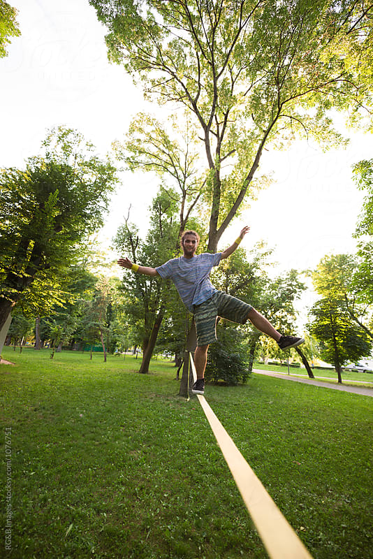 Happy young man slacklining in a green park  by RG&B Images for Stocksy United