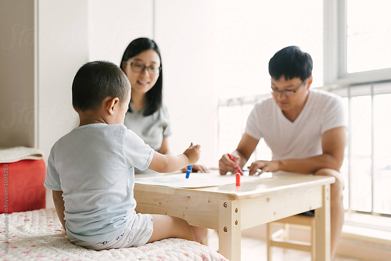 Toddler boy and his parents drawing at home by MaaHoo Studio for Stocksy United