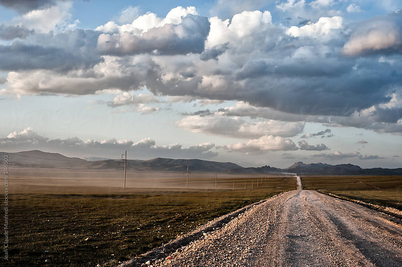 Dirt road in a prairie to the mountains of kyrgyzstan at sunset by Jean-Claude Manfredi for Stocksy United