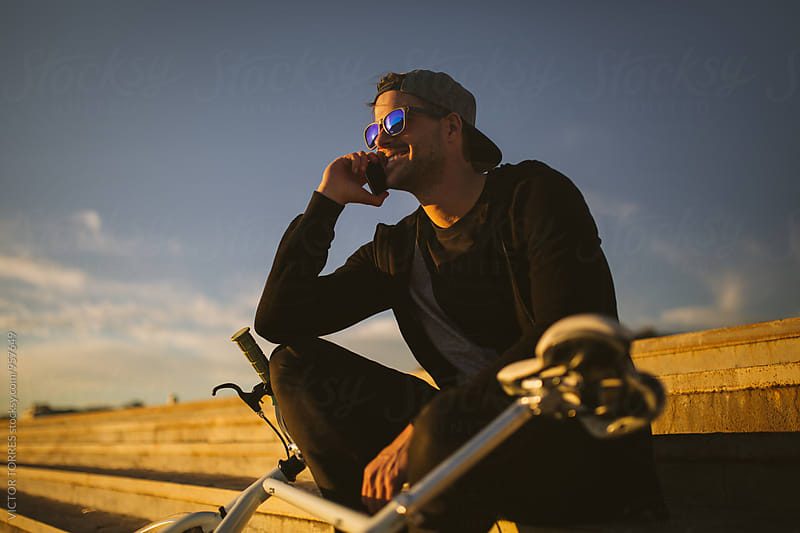Young Man Talking by Phone at Sunset Besides His Bicycle by VICTOR TORRES for Stocksy United