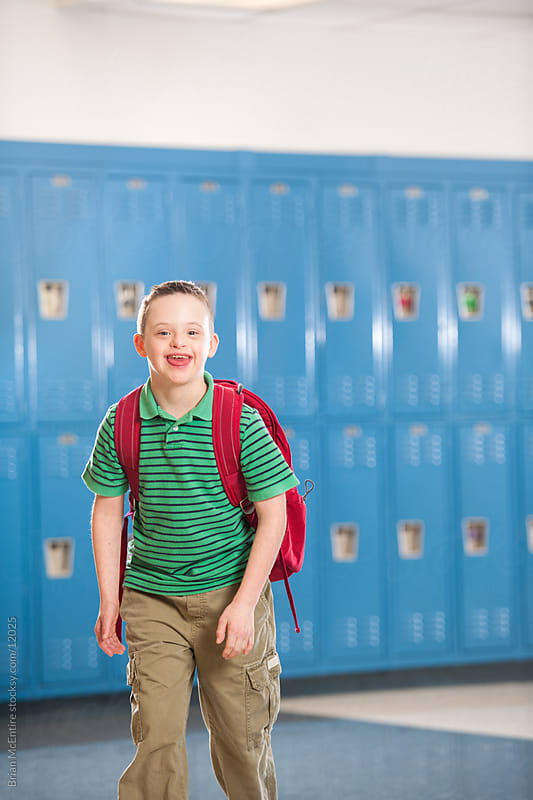 Fourth Grade Boy with Down Syndrome Proudly Walking Halls of School by Brian McEntire for Stocksy United