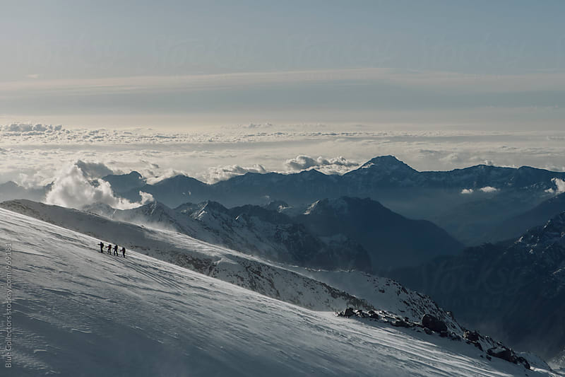 Group of skiers walking up the glacier in windy day by Jordi Rulló for Stocksy United
