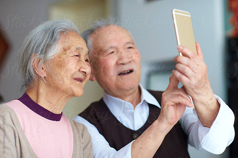 senior asian couple using smart phone indoor by Bo Bo for Stocksy United