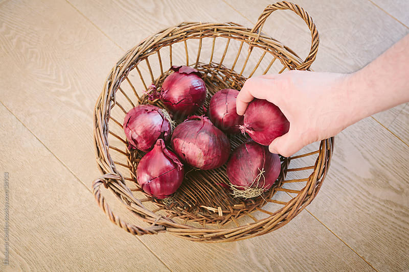 Man taking red onion out of a basket by Elisabeth Coelfen for Stocksy United
