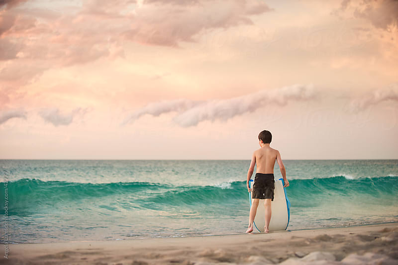 Young boy standing in front of waves at the beach at sunset by Angela Lumsden for Stocksy United