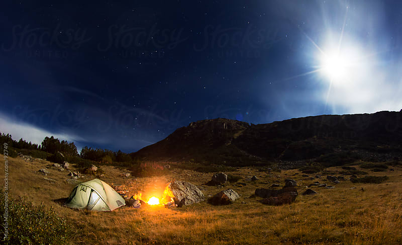 Fire near tent in cold mountains, stars above by Marko Milovanović for Stocksy United