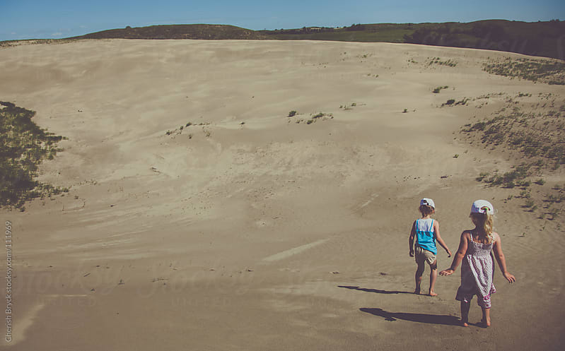 Two little girls run through the sand dunes. by Cherish Bryck for Stocksy United