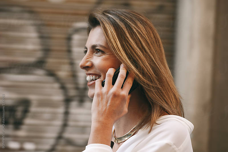 Close up of mature businesswoman talking with smartphone on urban street. by BONNINSTUDIO for Stocksy United