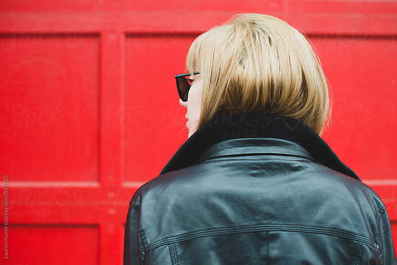 Young woman in leather jacket shot from behind by Lauren Naefe for Stocksy United