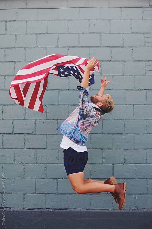 Young man jumping while holding the American flag by Chelsea Victoria for Stocksy United