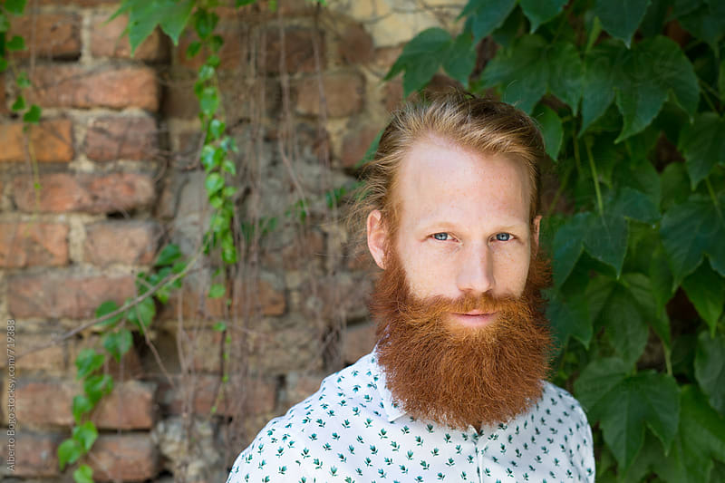 Man with long red beard portrait against brik wall by Alberto Bogo for Stocksy United