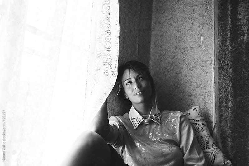 Portrait of a young woman sitting by the window by Natasa Kukic for Stocksy United