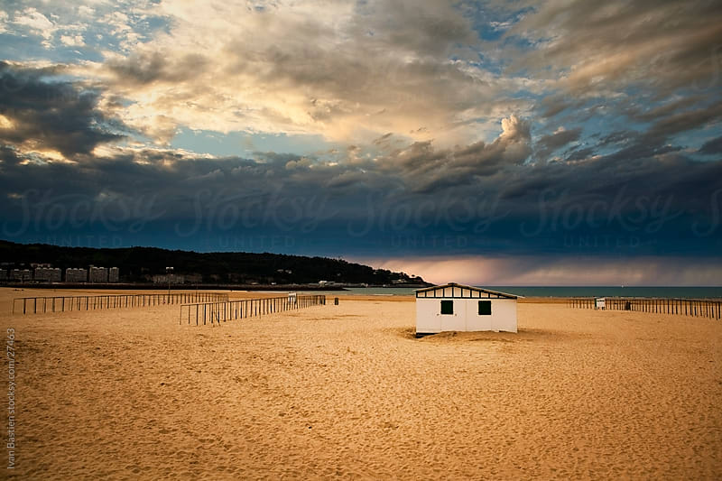 Hendaye beach with cabin and dramatic sky by Ivan Bastien for Stocksy United