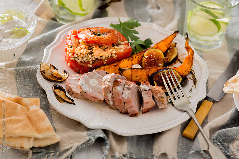 Pork Tenderloin Dinner with Sweet Potatoes and Stuffed Tomato by Studio Six for Stocksy United