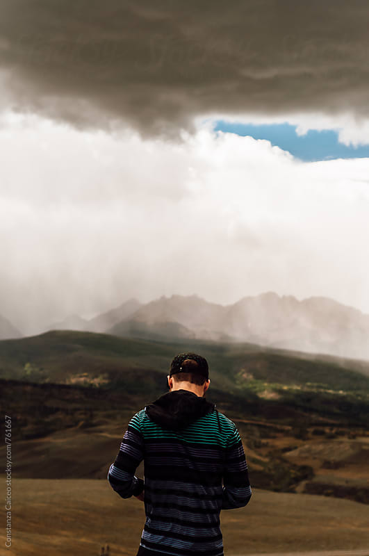 A young man staring at an upcoming storm in the mountains by Constanza Caiceo for Stocksy United