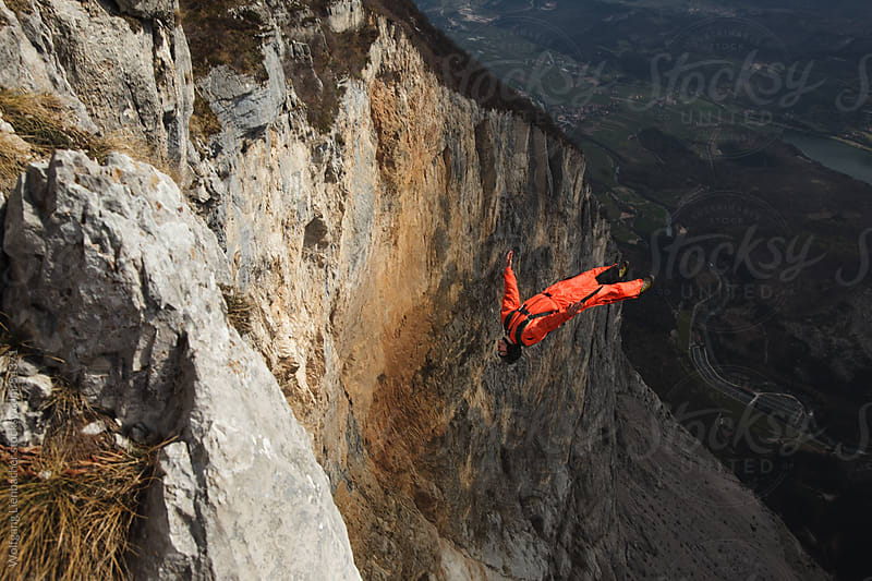 Basejumper exiting from a cliff performing a backflip  by Wolfgang Lienbacher for Stocksy United