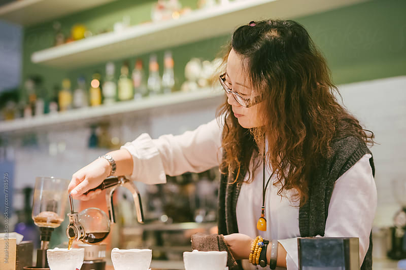 Female coffee shop owner preparing coffee at counter by MaaHoo Studio for Stocksy United