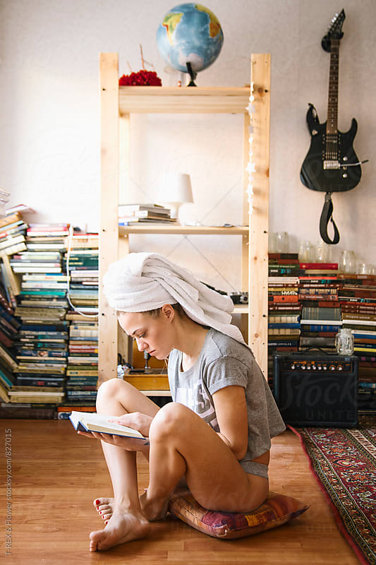Young woman with towel on head reading  book by Danil Nevsky for Stocksy United
