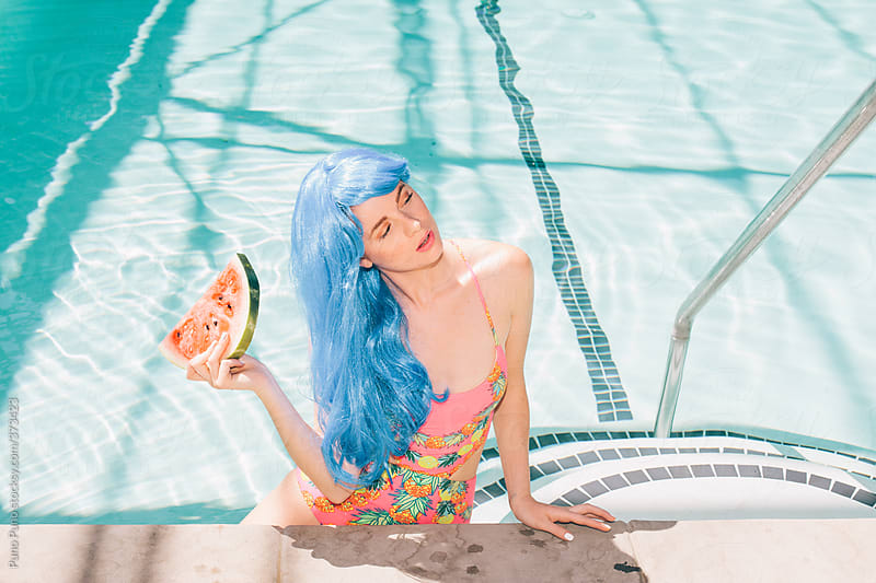 Girl eating by the pool. by Puno Puno for Stocksy United