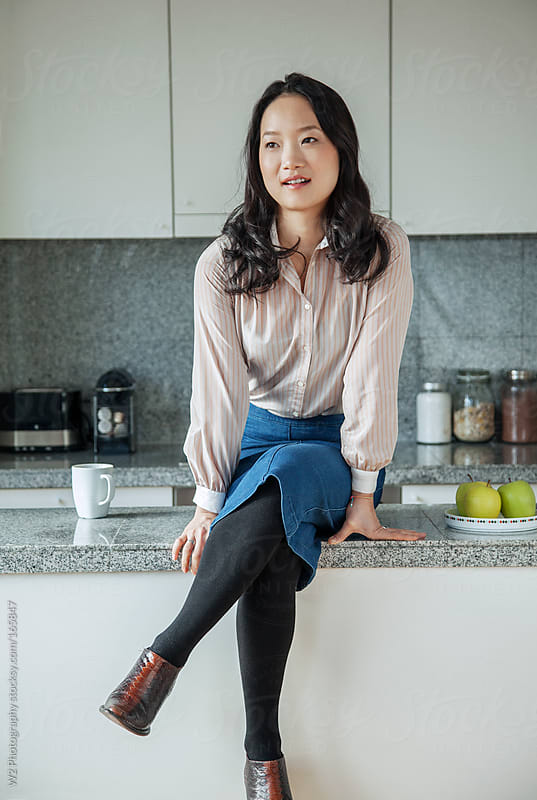 Portrait of a stylish woman in her sunny kitchen by W2 Photography for Stocksy United