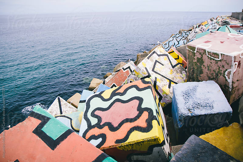 Graffiti painted cubes on dock next to the sea by Alejandro Moreno de Carlos for Stocksy United