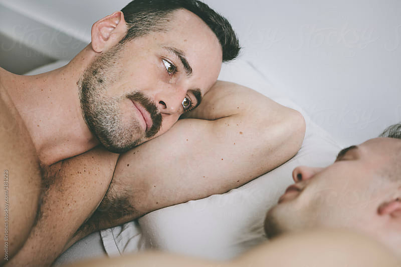 Gay Men Couple Waking Up in Bed Face to Face by Joselito Briones for Stocksy United