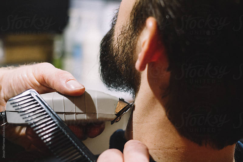 young man gets beard trimmed at barber shop by Jesse Morrow for Stocksy United