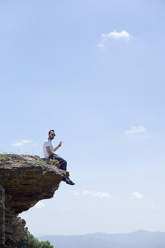 Young man sitting on a high rock by ACALU Studio for Stocksy United