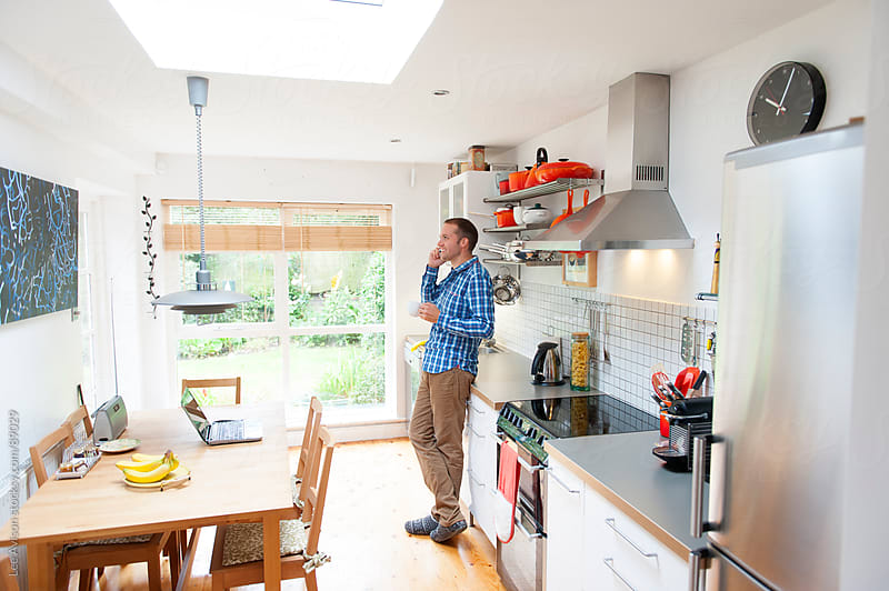 man chatting on his cell phone in the kitchen by Lee Avison for Stocksy United