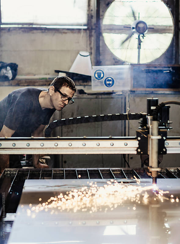 Young working man supervising plasma cutting machinery by Lior + Lone for Stocksy United