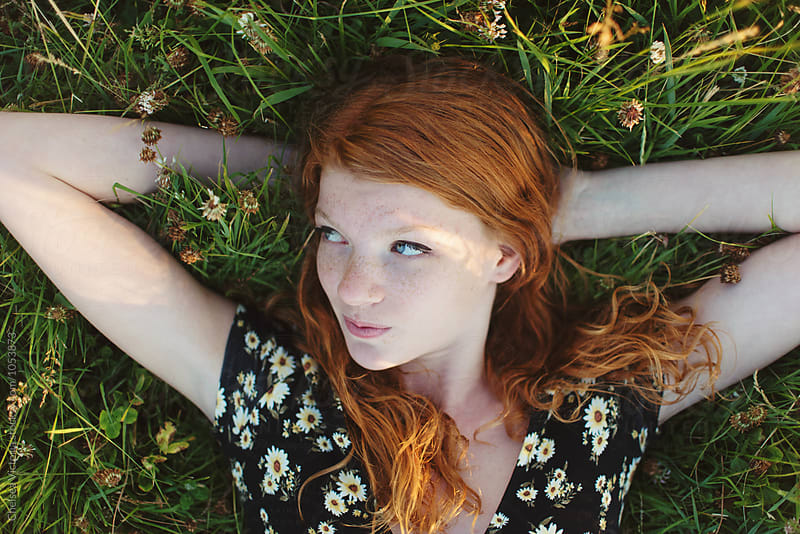 A teenage girl laying in a field in the summertime by Chelsea Victoria for Stocksy United