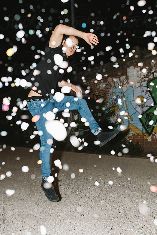 Cool asian man jumping under a confetti rain by GIC for Stocksy United